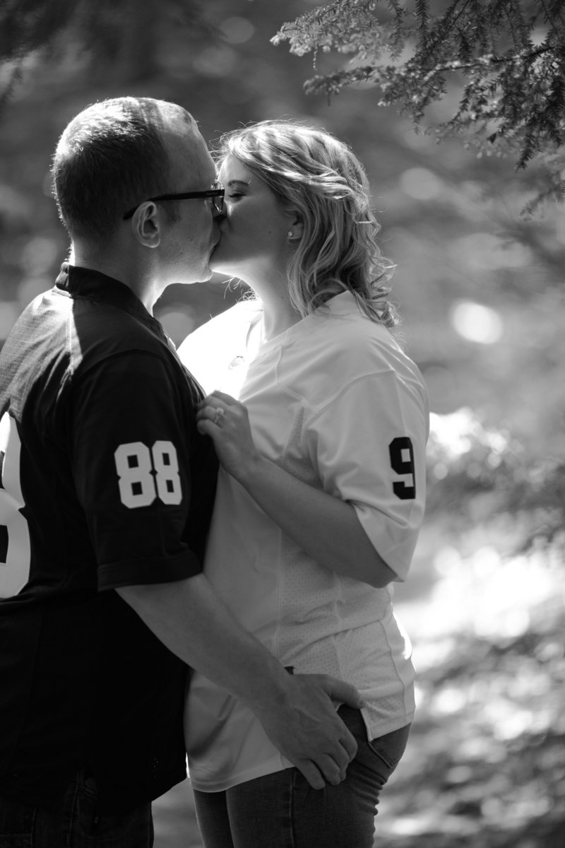 Engaged couple kisses in the trees during summer engagement photos at Penn State Erie
