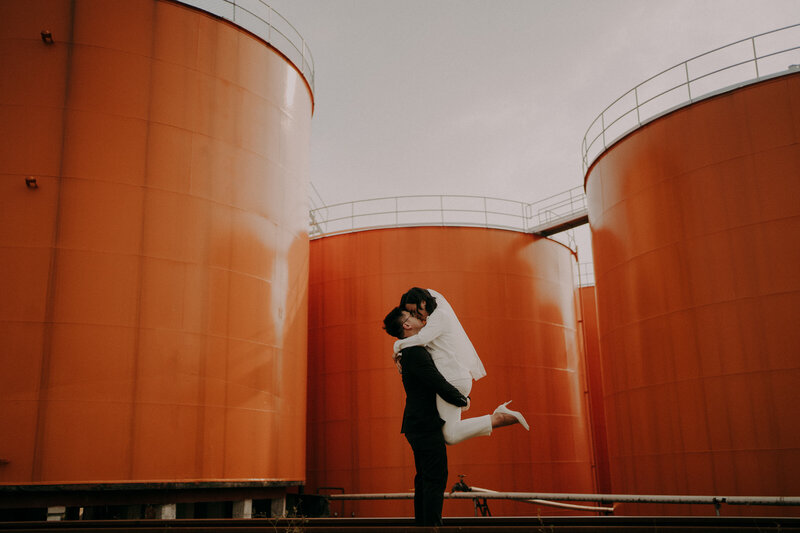 couple kissing in front the oil tank