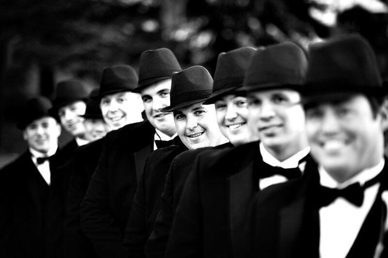 A creative photo of the groomsmen wearing fedora hats and black bow ties.