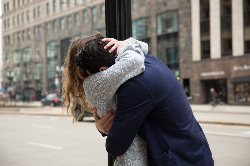 couple hugging after surprise proposal woman gasping from surprise engagement downtown chicago mag mile