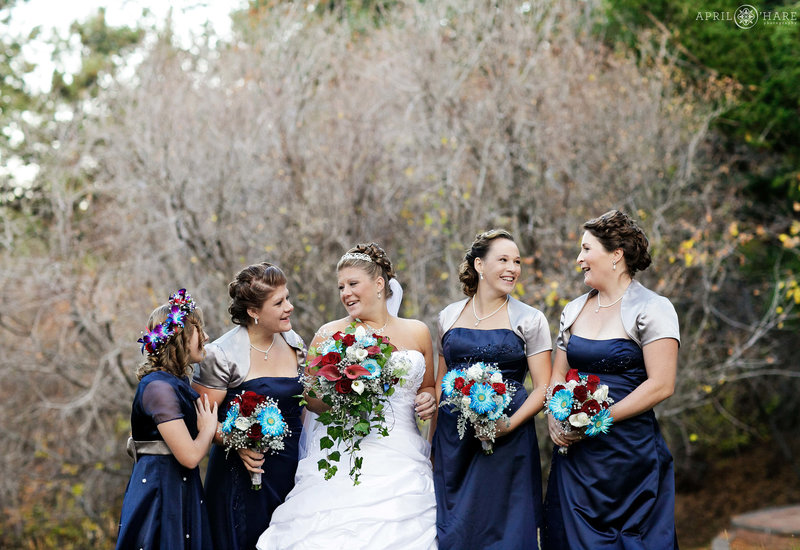 Bridesmaids wearing satin navy blue dresses at a fall wedding at The Pines at Genesee in Colorado