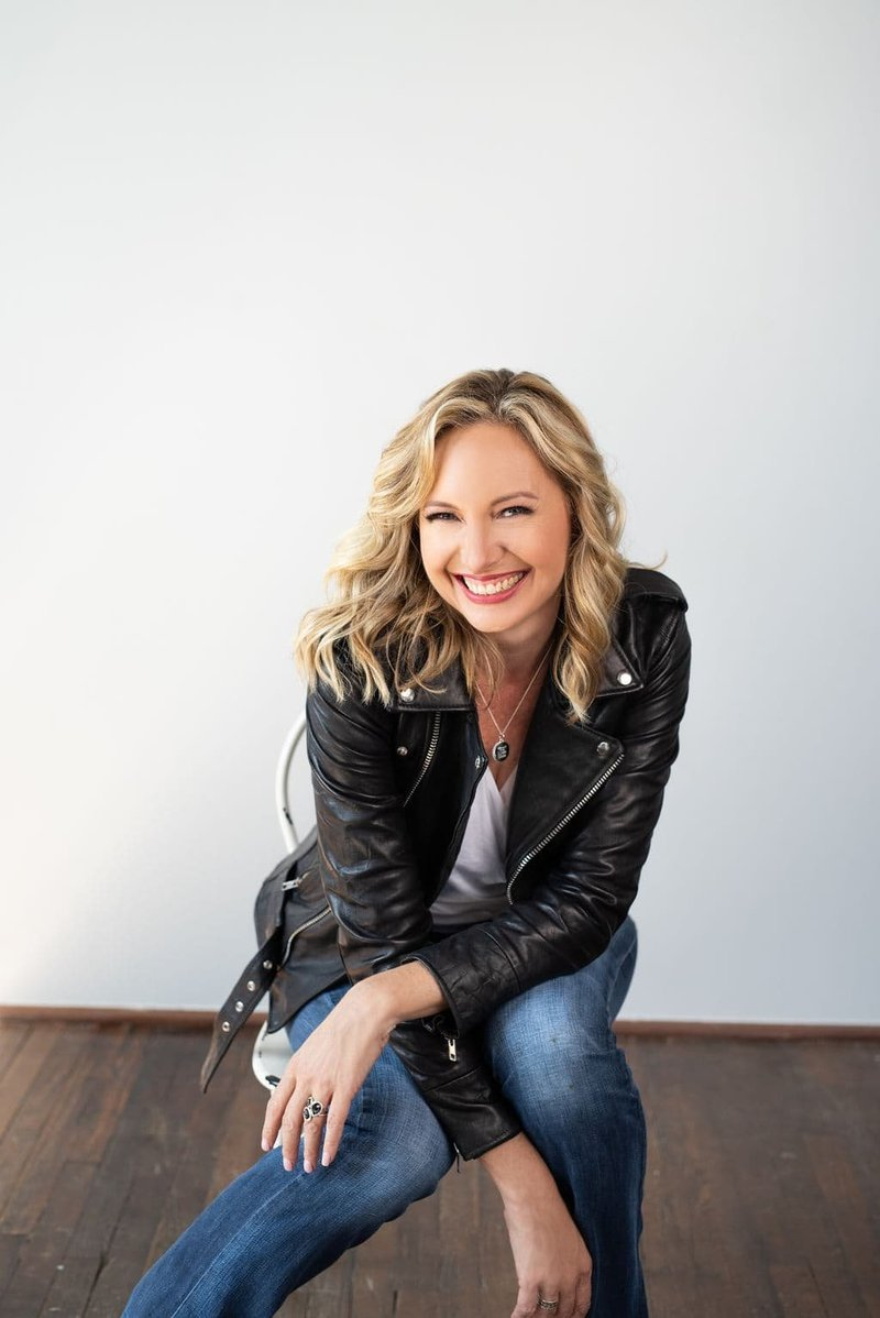 Jen Denton smiling wearing a black leather jacket and jeans