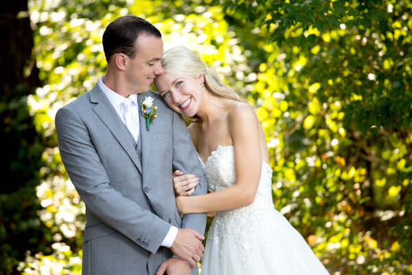 Bride and groom hold each other and smile in a closeup at Hidden Acres