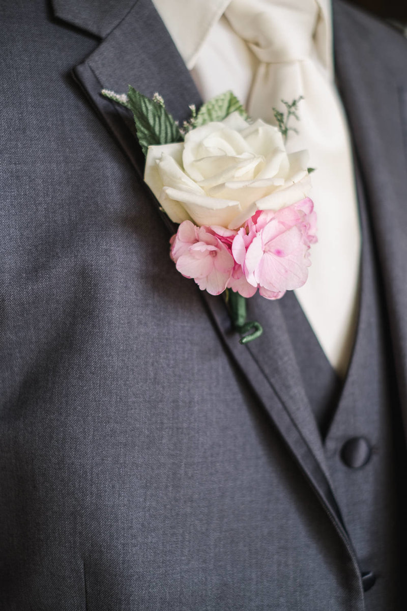 Groom's white rose and pink flower boutonniere