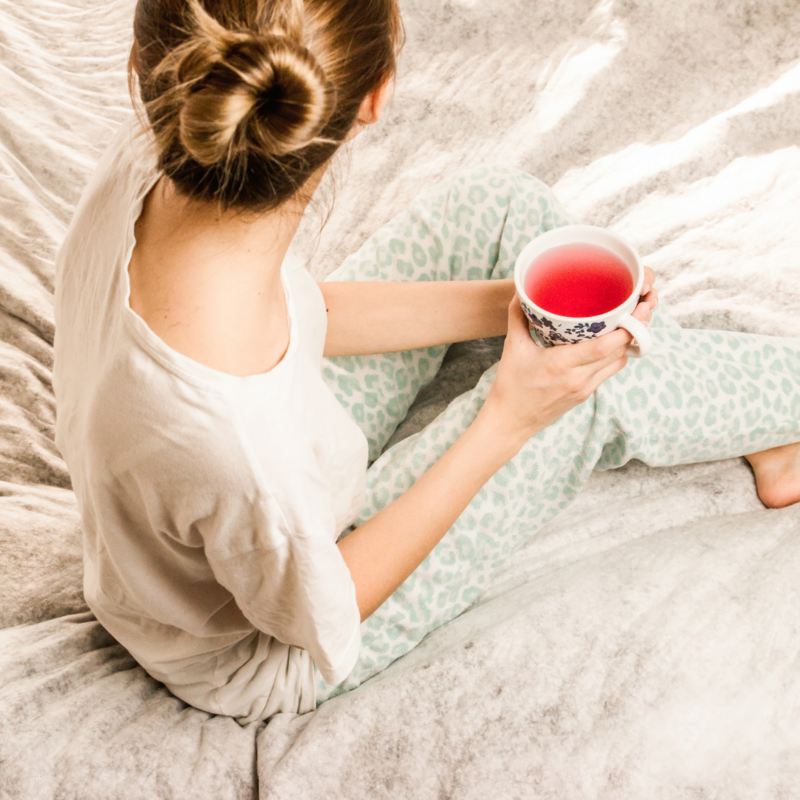 A woman sipping on tea in her pjs on  her bed relaxing