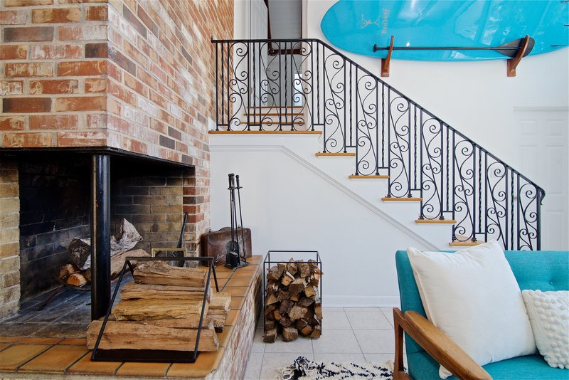 A fireplace and a paddleboard both find a home in this midcentury modern and bohemian influenced living room by Denver based interior designer Fernway & Avalon