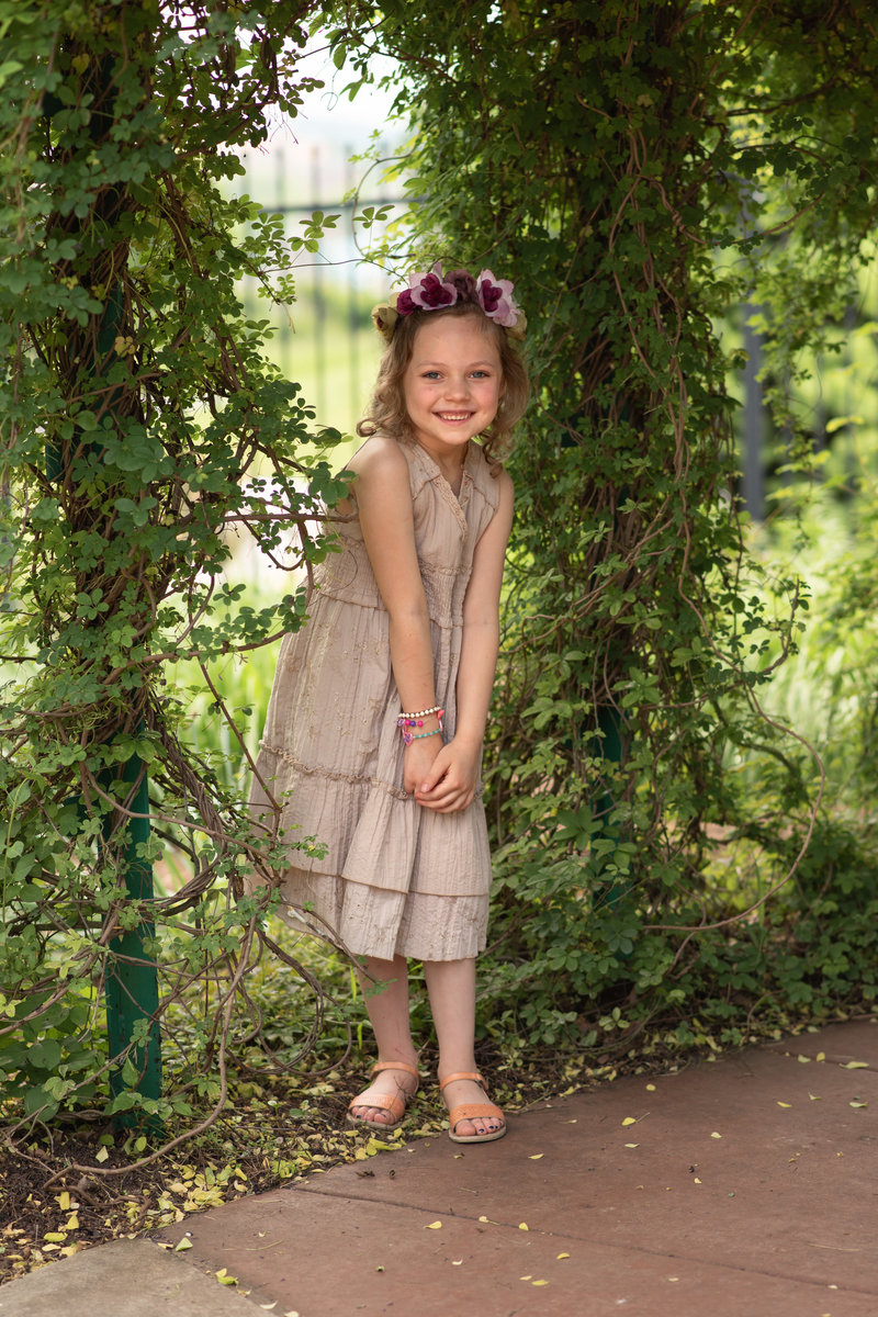 Little girl in brown dress standing near vine-covered gate
