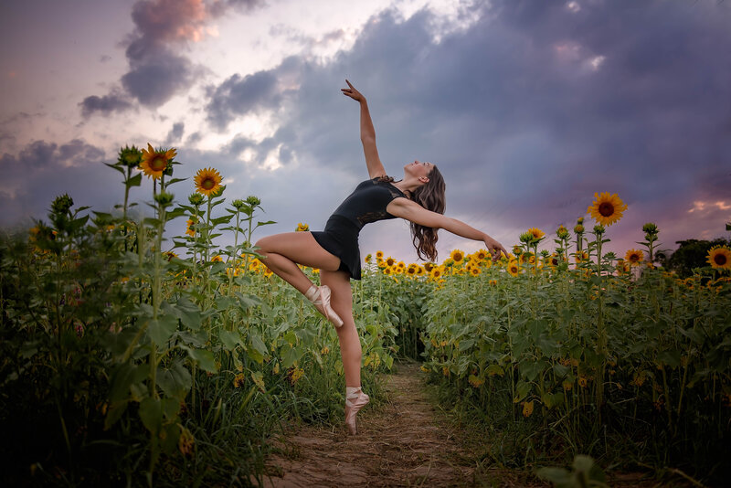 Dancer dancing in sunflower field at sunset