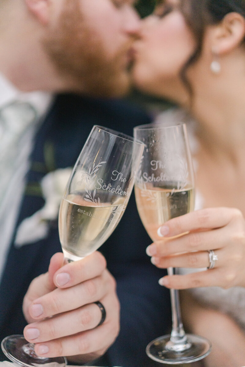 champagne glasses toasting as bride and groom kiss in the background