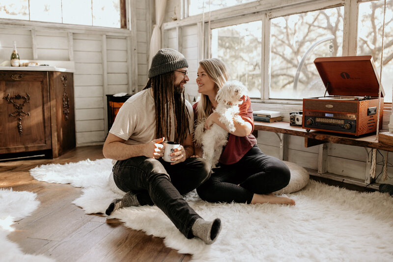 Man with dreads, beanie, and glasses smiles big at his wife while they both sit down on the floor. Wife is holding a little white fluffy dog with a beaming smile as she looks at her husband