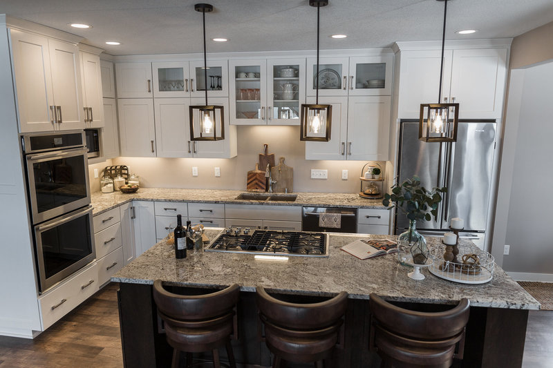 white kitchen with pendants and wood island