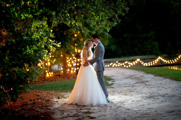 Bride and groom hold each other close in front of lighted trees at Hidden Acres