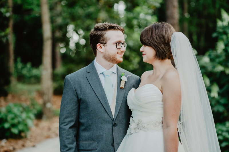 Bride and Groom look longingly at each other after first look at Aldridge Gardens, in Hoover Alabama