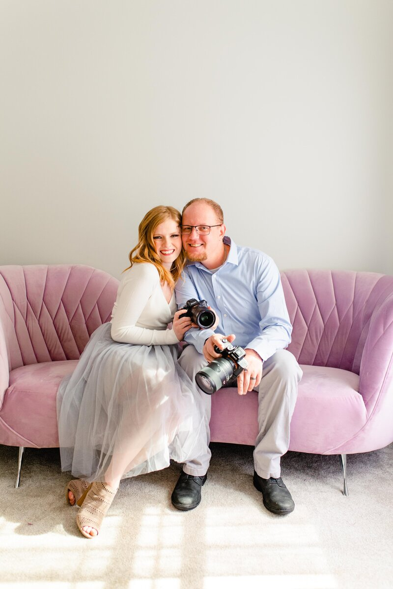 Wedding photographers holding cameras together in purple home office