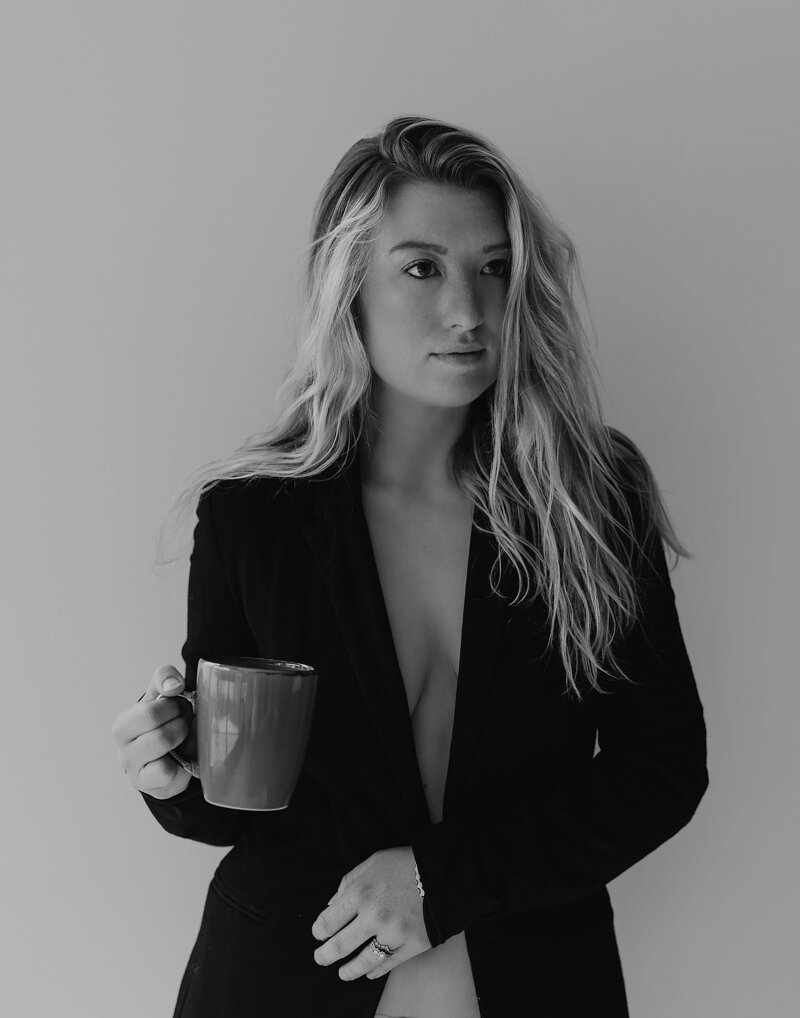 Cate Autumn holding a coffee mug and wearing a blazer