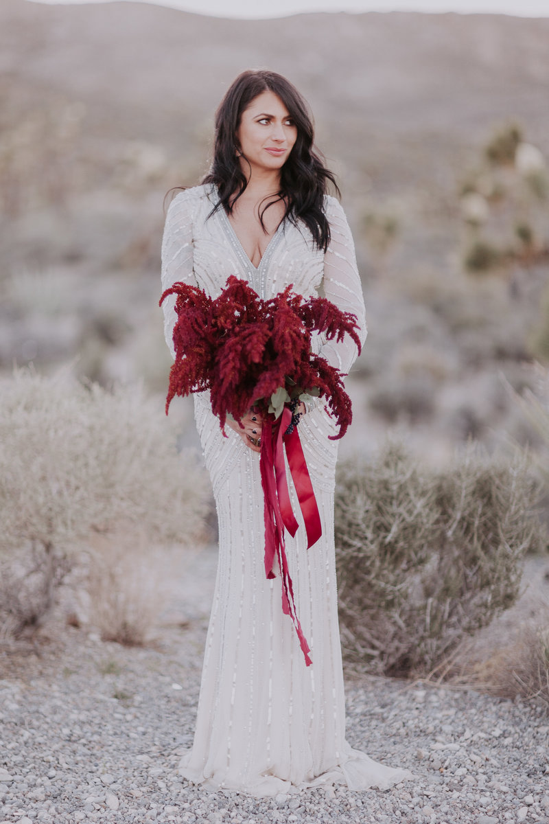 Lake Tahoe wedding pictures a bride poses with her burgandy bouquet in the desert