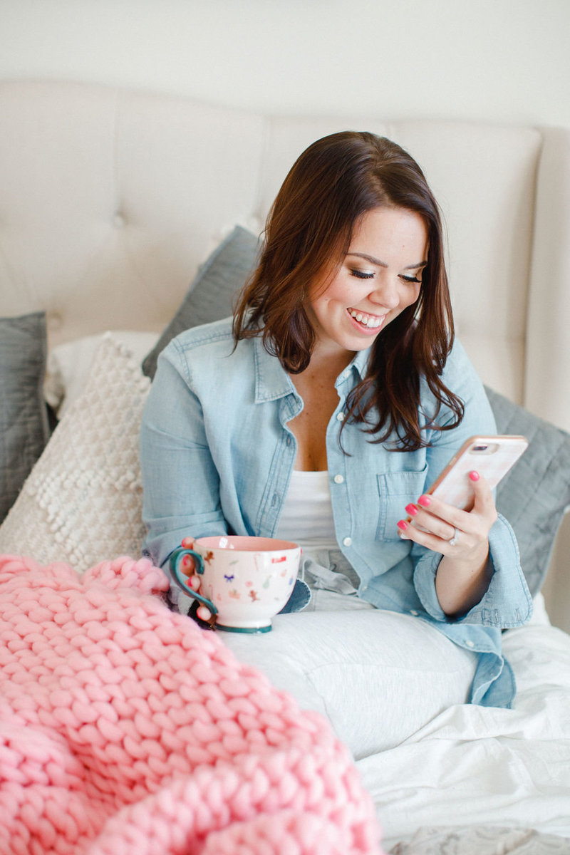 A woman on her phone with tea