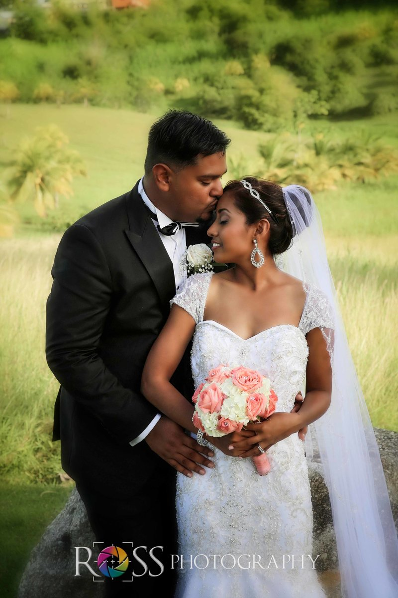 Groom kisses bride's forehead.. Photo by Ross Photography, Trinidad, W.I..