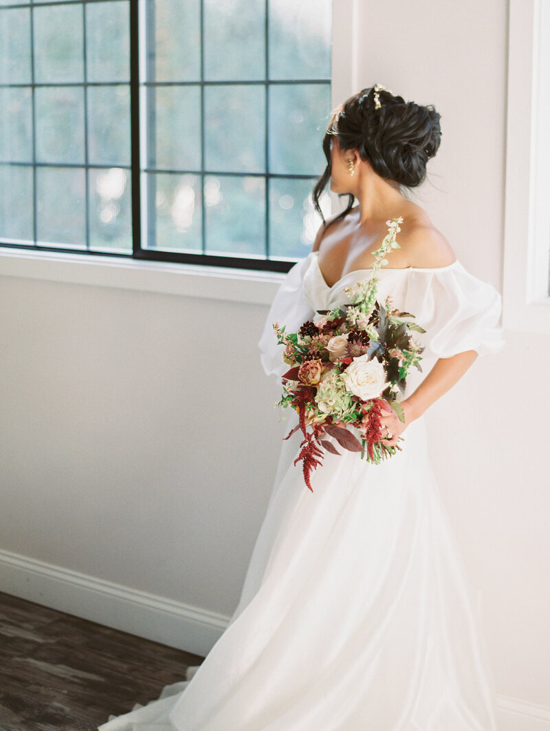 Bride wears braided bun and looks away from camera holding bold floral bouquet