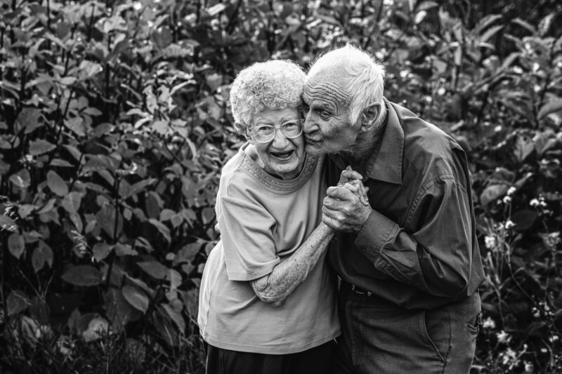 black and white image of elderly husband kissing his wifes cheek