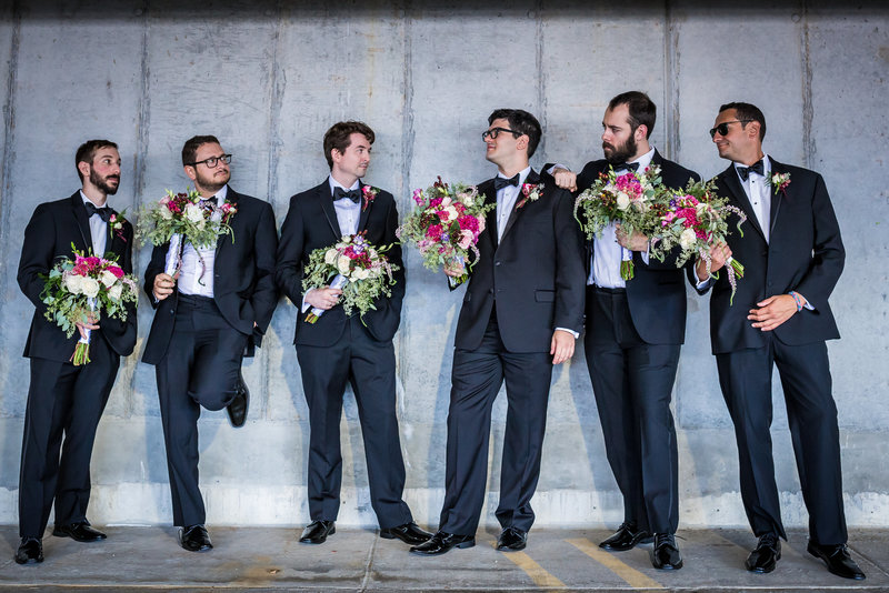 Photo of groom and groomsmen holding flowers at the Cira Green garage in Phildelphia PA