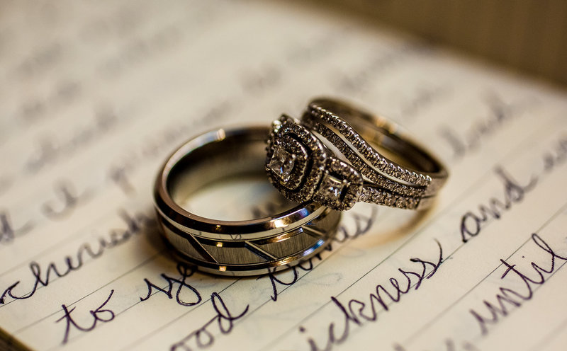 Wedding rings placed on handwritten vows