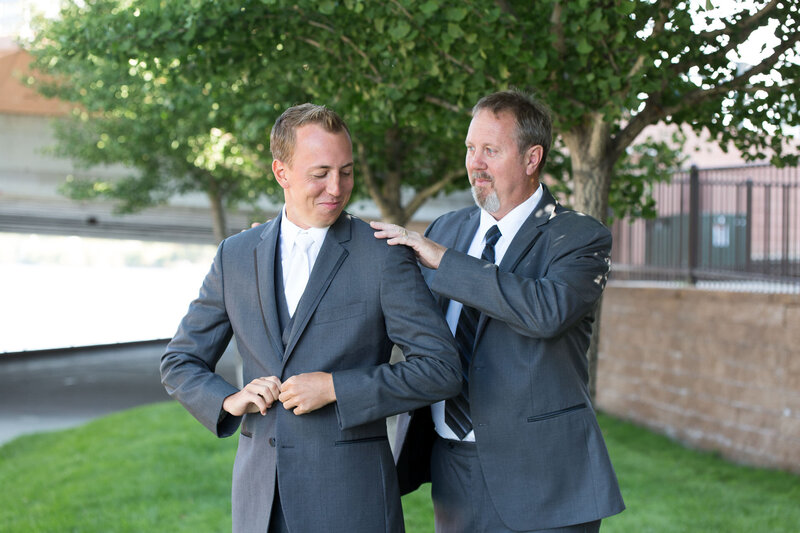 father helping son put on suit on wedding day in downtown detroit