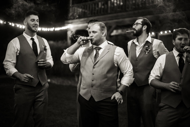 Groom and his groomsmen smoking cigars outside at Rustic Acres Farm