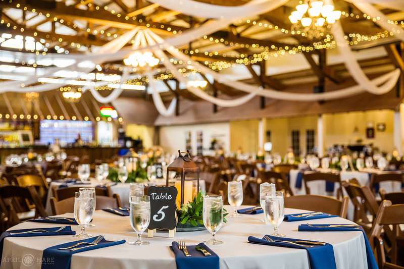 Inside the Great Hall at Church Ranch Event Center with tables decorated with lanterns and blue napkins