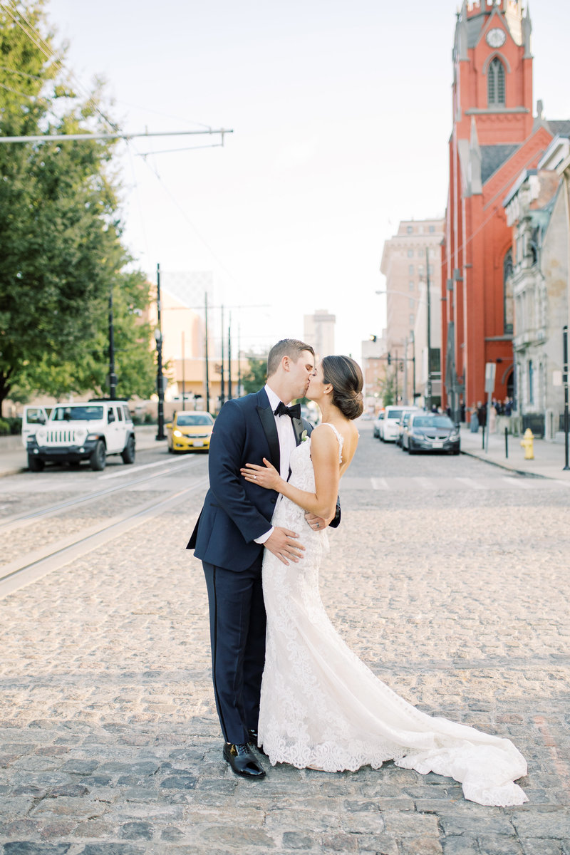 A couple leans back into a kiss in the middle of a cobblestone street on their wedding day in  Cincinnati, Ohio
