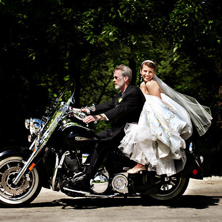 Bride riding on the back of a motorcycle with her dad.  By Kansas City Photographers