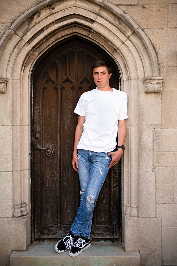 High school senior boy standing in doorway of stone mansion at Hartwood Acres in Pittsburgh, PA