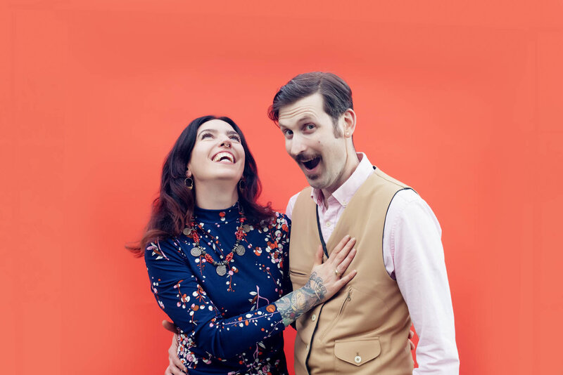 a silly and fun couple pose for the camera  in front of a bright orange wall during their engagement photos