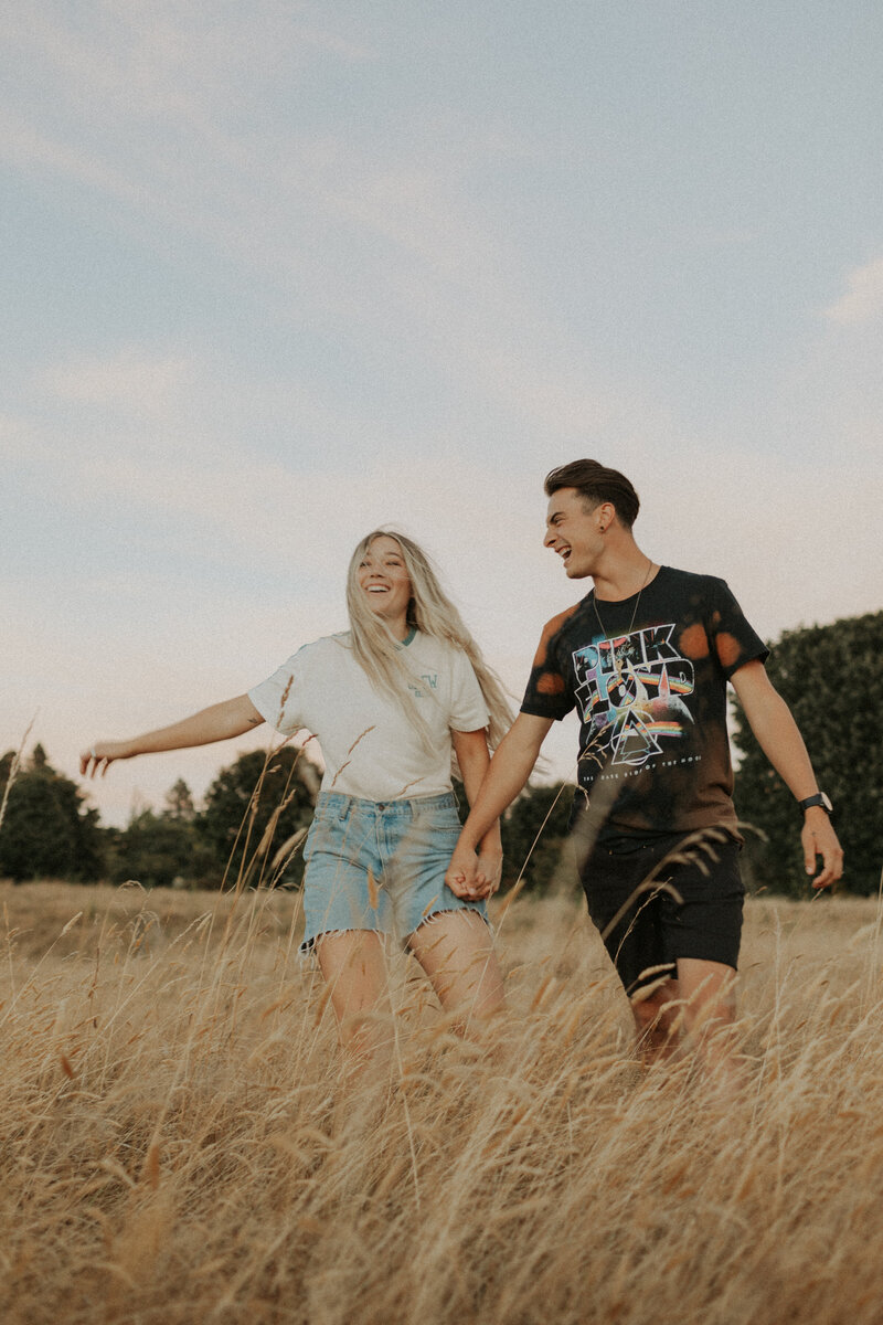 Couple holding hands and walking toward the camera in a field during their couple photos