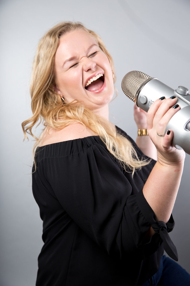 Victoria Sneden Singing into Podcast Microphone