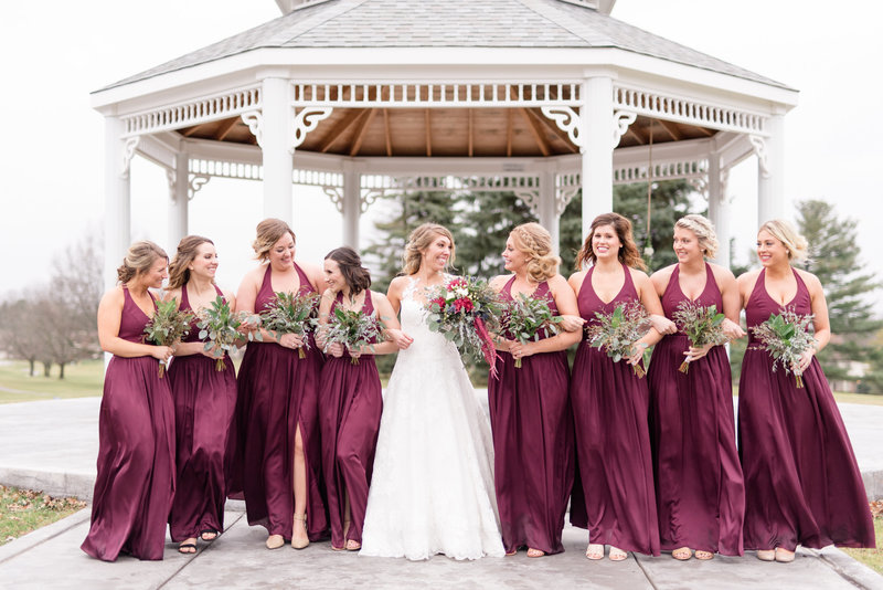 Bridal party walks together with linked arms.