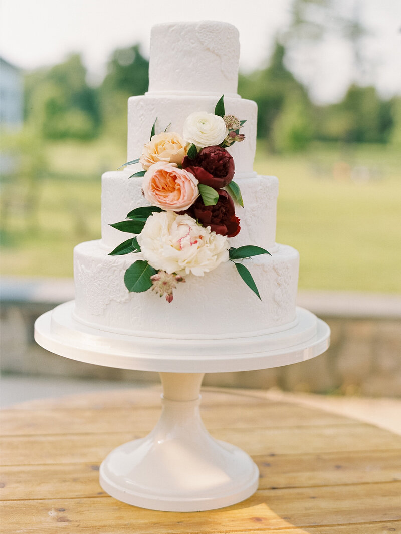 Simple white wedding cake with florals and lace design