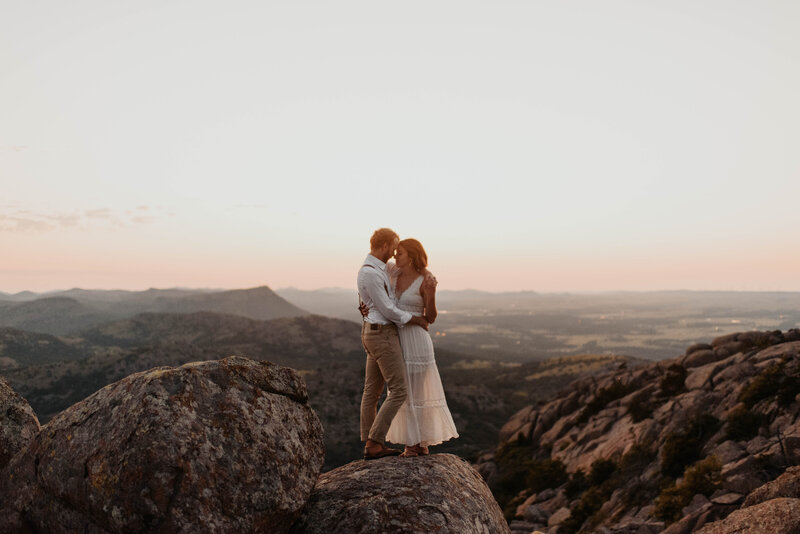 couple holding eachother standing on a mountain