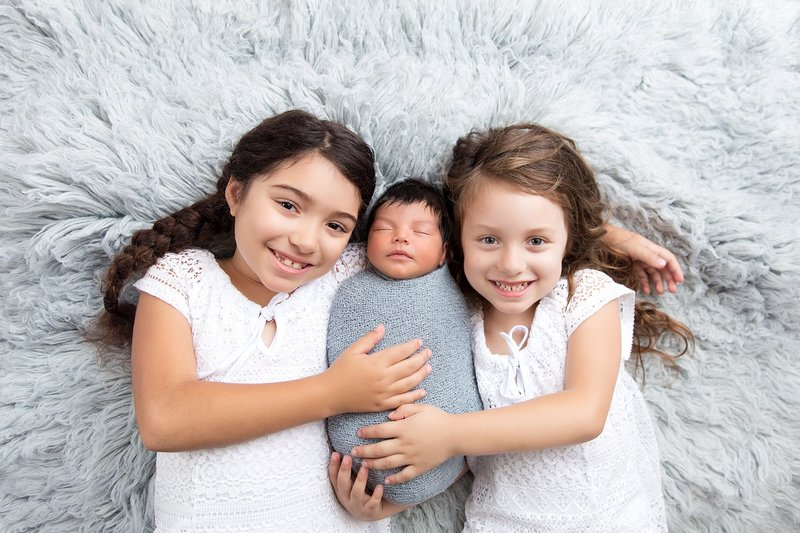 Sisters with baby brother blue
