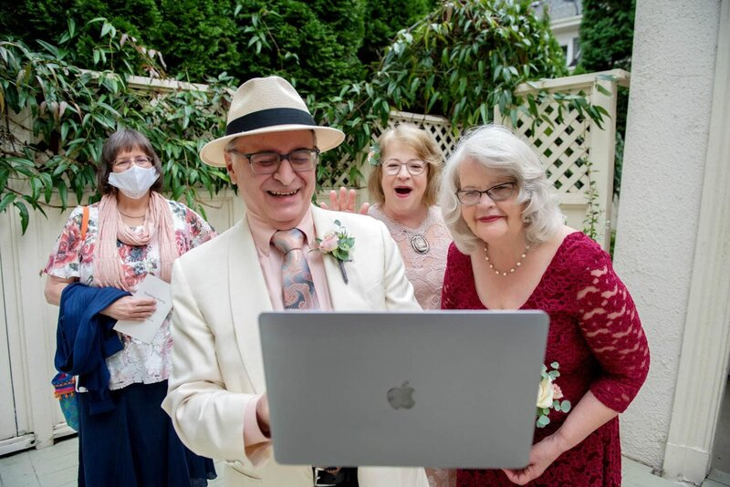 an older couple looks excitedly on the apple computer to talk to guests who joined their wedding via zoom
