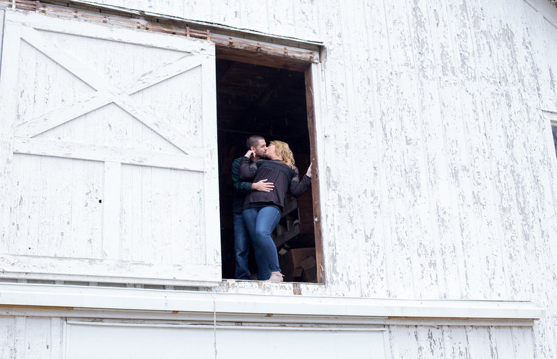 portrait of engaged couple kissing inside the doorway of a white barn at the Barn at Conneaut Creek in Albion, PA
