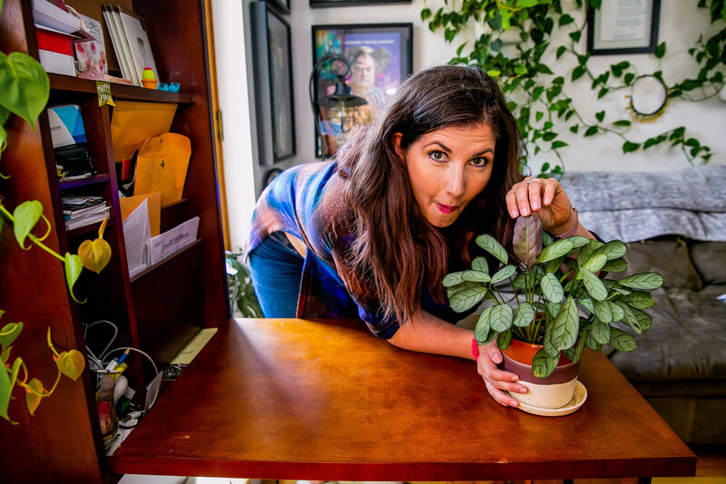 Maria, host of Bloom & Grow Radio, admires a favorite plant in her apartment