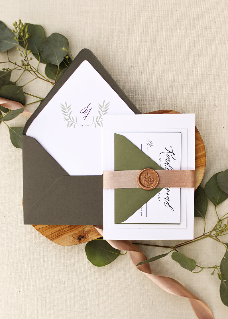A subtle watercolor eucalyptus leaf adorns the bottom of the invitation. Paired with beautiful typography and modern calligraphy, this invitation is perfect for any wedding. Shown with envelope liner, ribbon & Wax seal