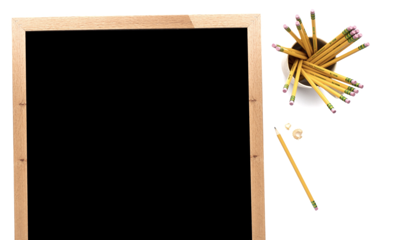 Black chalgboard with wooden border beside  pencils in a pencil holder with a pencil on the side that has been sharpened.