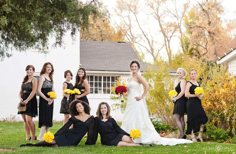 Bride with bridesmaids outside of white rustic farmhouses at Chatfield Farms Denver Botanic Gardens in Denver