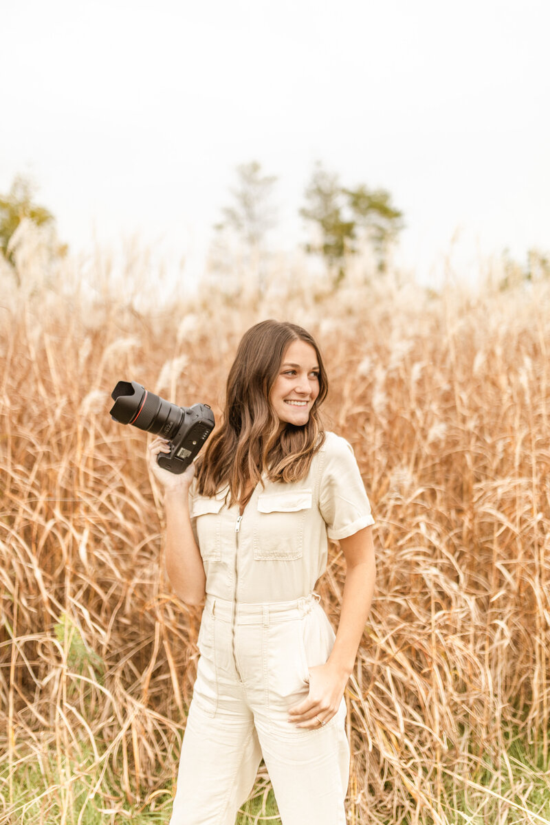 woman standing in tall grass holding a camera