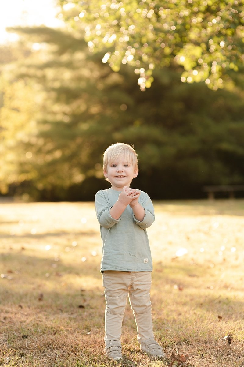 A little toddler boy is clapping his hands for a photo  and smiling at the camera for his family portraits in Green Hills Nashville Tennessee