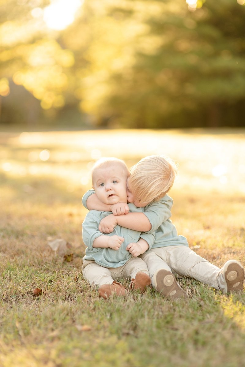 An older brother is hugging his baby brother very tightly for family portraits in Nashville Tennessee in the golden hour