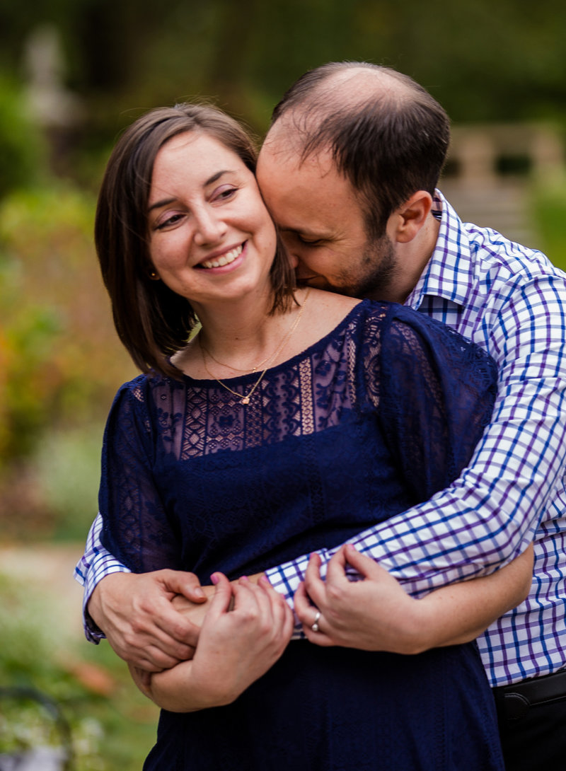 Man nuzzles fiancee's neck at Mellon Park engagement portraits session