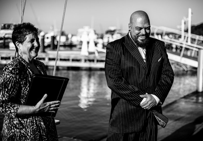 Groom and officiant smiling as they see the bride at an Erie Yacht Club wedding